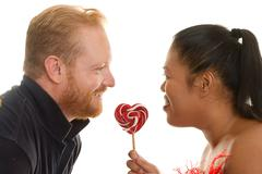 Two people share a candy - stock photo