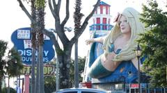 Mermaid, lighthouse & Disney store sign through trees Stock Footage