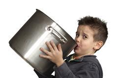 Child drinking milk from a big saucepan Stock Photos