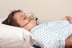 Unwell child oxygen mask Stock Photos