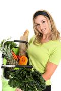 Woman displaying bag full of groceries Stock Photos