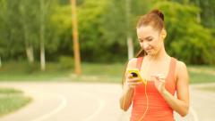 Young woman running with headphones and music player, Ultra HD 4K video - stock footage