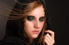 Black makeup and hood on a beutiful young girl - stock photo