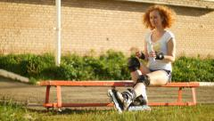Young girl with rollerblades drinking water Stock Footage