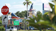 Wizard's head (store sign) with stop sign and palm trees in foreground Stock Footage