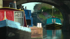 Narrow boats moored up reflected in water under arch bridge Stock Footage