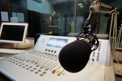 Mic in front of the control panel in broadcasting studio Stock Photos