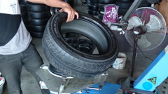 Changing tyre: Man placing new tyre on a tyre changing machine in a garage Stock Footage