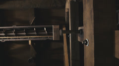 Slider shot moving past turning belts and gears in corn mill. Stock Footage