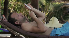 Man sending message on sunbed in exotic place Stock Footage