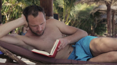 Man reading book and lying on sunbed Stock Footage
