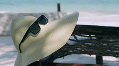 Hat and sunglasses hanging on the sunbed Stock Footage