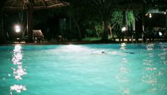 Man swiming in a pool at night, swimming pool, steadycam shot Stock Footage