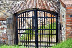 old closed gate into the castle - stock photo