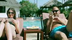Couple checking cellphones, swimming pool, steadycam shot Stock Footage