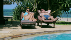 Woman using cellphone lie on a sun lounger in swimming pool Stock Footage