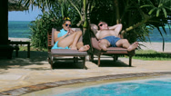 Stock Video Footage of Woman using cellphone lie on a sun lounger in swimming pool