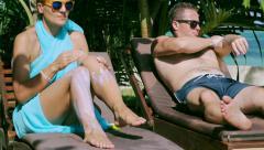 Couple using sun cream and lying on sunbeds Stock Footage
