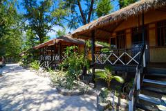tropical beach bungalow on ocean shore - stock photo