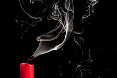 smoke from blown out red candle - stock photo