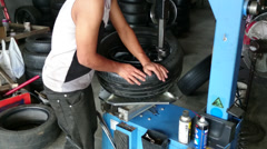 Changing tyre: Man placing a new tyre on a wheel rim using machine and pry bar Stock Footage