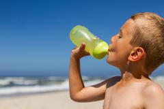 Thirsty boy drinking from water bottle Stock Photos