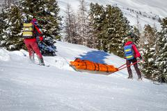 ski patrol helping injured skier - stock photo