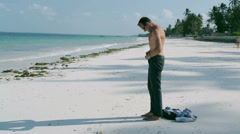 Businessman taking off his trousers on the beach, steadycam shot Stock Footage