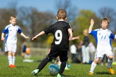 boy dribbling during soccer match - stock photo