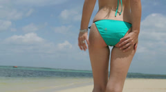 Woman cleaning her bottom on the beach Stock Footage