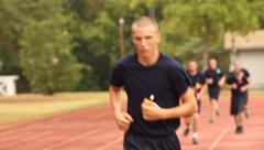 Alert Academy recruits run laps around a track Stock Footage