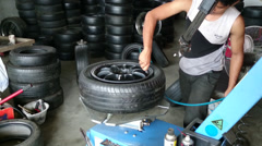 Changing tyre: Man inflating new tyre using air compressor Stock Footage