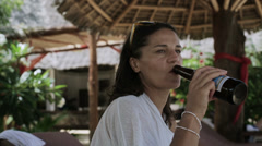 Woman drinking beer in exotic place, steadycam shot Stock Footage
