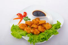 Stock Photo of Breaded chicken pieces served with sauce