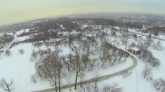 Park covered by snow with cityscape on horizon. Aerial view Stock Footage