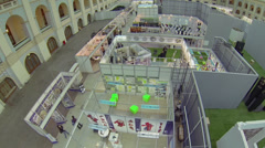 People walk by exposition in hall of exhibition center Stock Footage