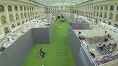 People and exhibits on green carpet between rows of pavilions Stock Footage