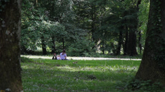 24 Park idyll. Two girlfriends enjoying a patch of sunshine. Stock Footage