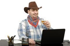 cowboy talking with friends on skype - stock photo