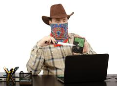 cowboy holding a knife and hard disk threats on skype - stock photo