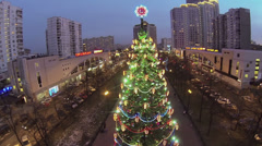 People walk near christmas tree with garland on street Stock Footage