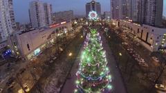 People walk near christmas tree with garland on street - stock footage