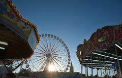carousel and ferris wheel  at dusk - stock photo