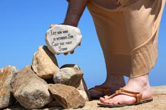 Man holding rock with bible verse John 8:7 - stock photo