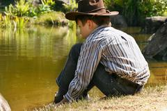 Child sitting by outback billabong - stock photo