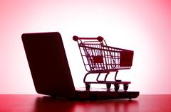 Silhoette of laptop and shopping cart Stock Photos