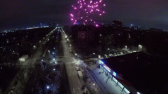 Fireworks flash and sparkles against cityscape at winter night Stock Footage