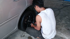 Changing tyre: Man tightening lug nuts of a new tyre using impact wrench Stock Footage