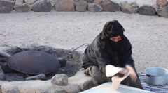 A woman bakes homemade bread on fire, in Beduin Camp near Mount Sinai, Egypt Stock Footage