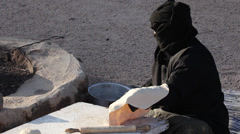 A woman rolls out the bread dough, in a Beduin Camp near Mount Sinai, Egypt Stock Footage